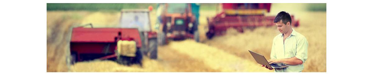 Man viewing laptop screen in front of background image of farm vehicles in a field
