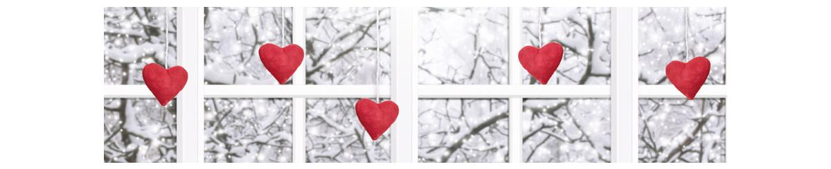 Hearts hanging in front of window with snow covered trees seen through the glass
