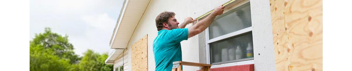 Man measuring window for plywood cover