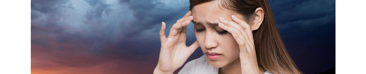 Woman suffering from headache pain with storm clouds in background