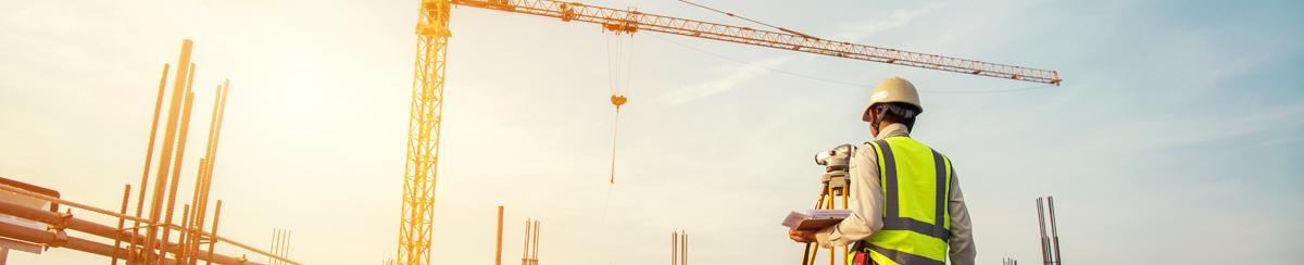 Man at construction site viewing crane