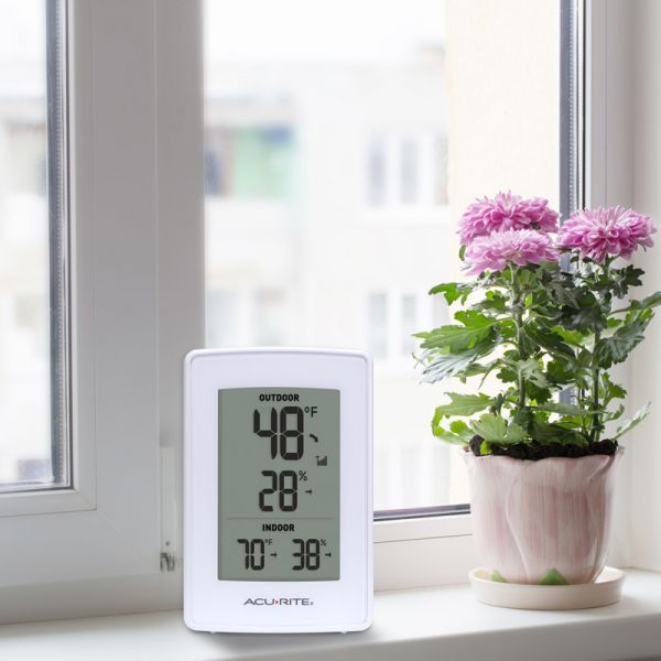White Indoor Outdoor Digital Thermometer and Humidity Gauge on a window ledge - AcuRite Weather Monitoring Devices