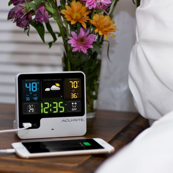 Alarm Clock with Weather Forecast sitting on a bedside table next to flowers - AcuRite Clocks