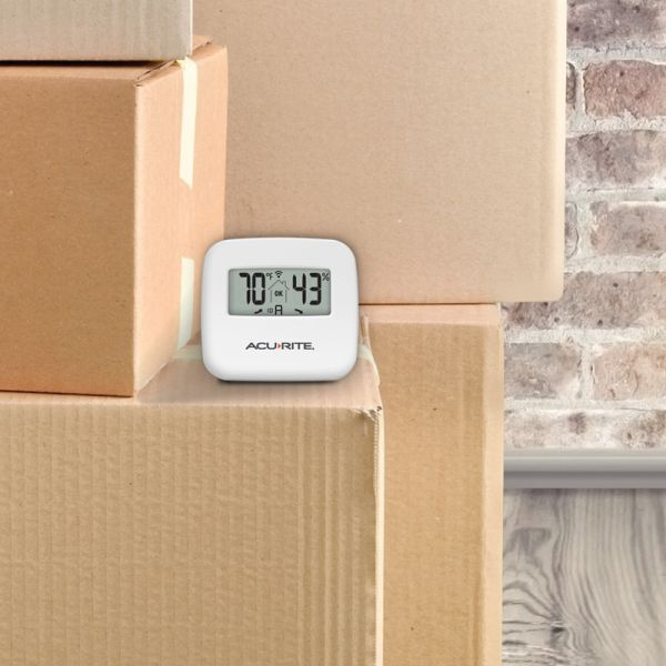 Indoor Temperature and Humidity Monitor sitting on boxes - AcuRite Home Monitoring Devices