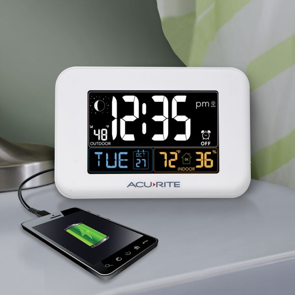 AcuRite Inteli-Time digital alarm clock with a phone charging next to a bed