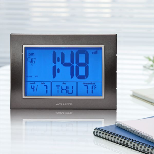 7-inch Atomic Alarm Clock with Date, Day of Week and Temperature on a desk with the backlight on - AcuRite Clocks