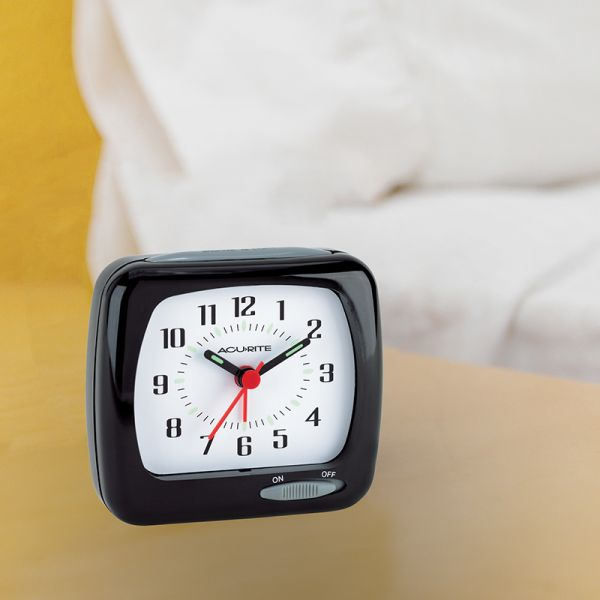 AcuRite travel alarm clock with glow in the dark hands sitting next to a bed on a table