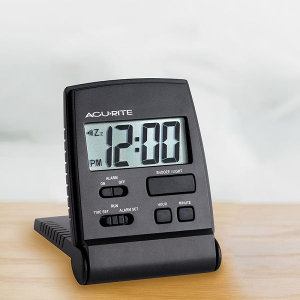 AcuRite travel alarm clock with snooze button on a table