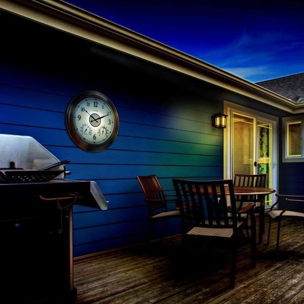 AcuRite 24-inch illuminated outdoor clock with temperature and humidity sensors hanging outside at night