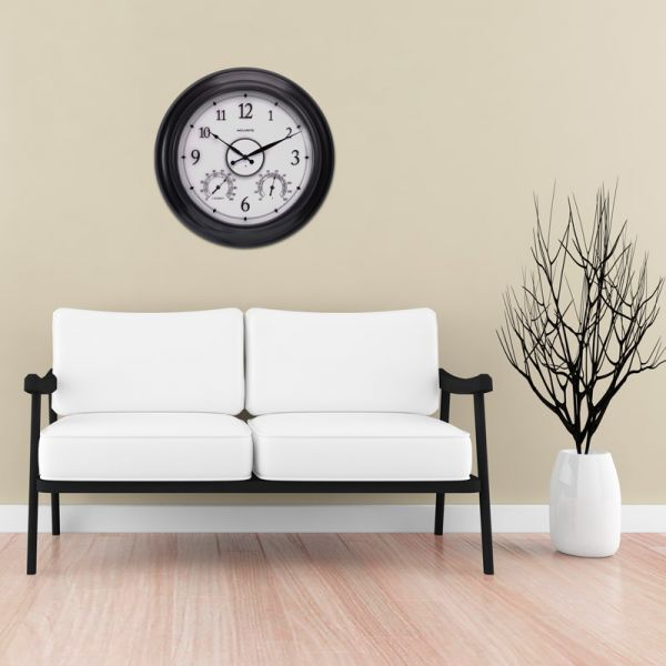 AcuRite 24-inch illuminated outdoor clock with temperature and humidity sensors hanging in a living room