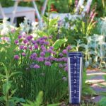 Easy-Read 12.5-inch Magnifying Rain Gauge in a garden on a sunny day - AcuRite Weather Monitoring Devices