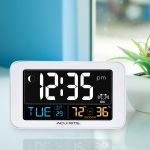 AcuRite digital alarm clock sitting next to a window