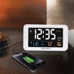 AcuRite digital alarm clock with USB charger sitting on a table