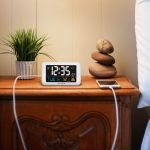 AcuRite digital alarm clock with USB charger on a bedroom table