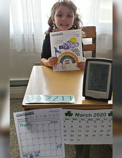 Girl holding coloring page at desk with weather display