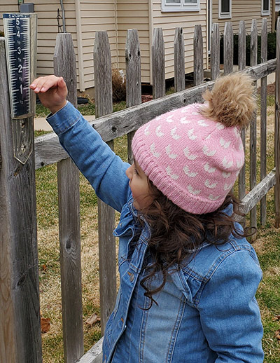 Girl checking rain gauge on fence