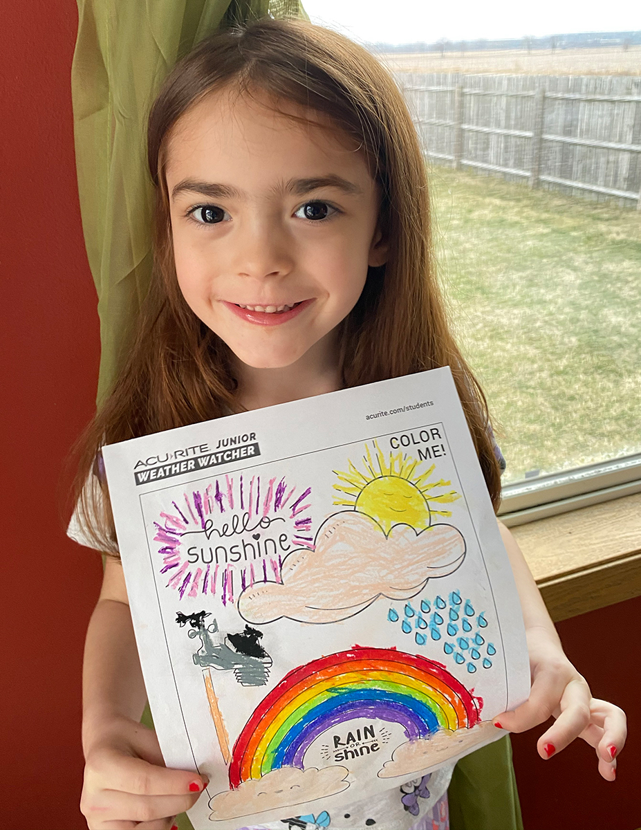 Girl holding coloring page in front of window