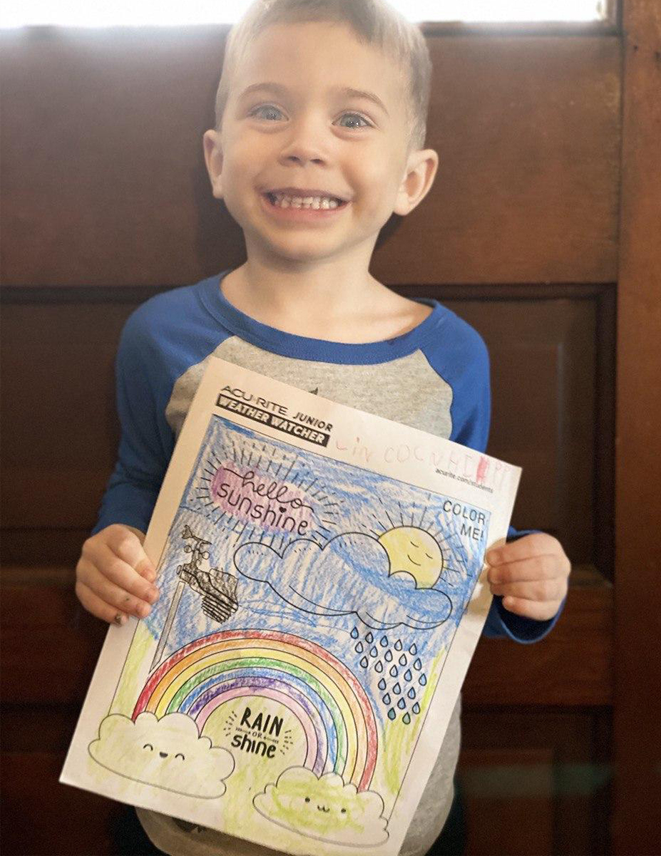 Boy holding coloring page in front of door