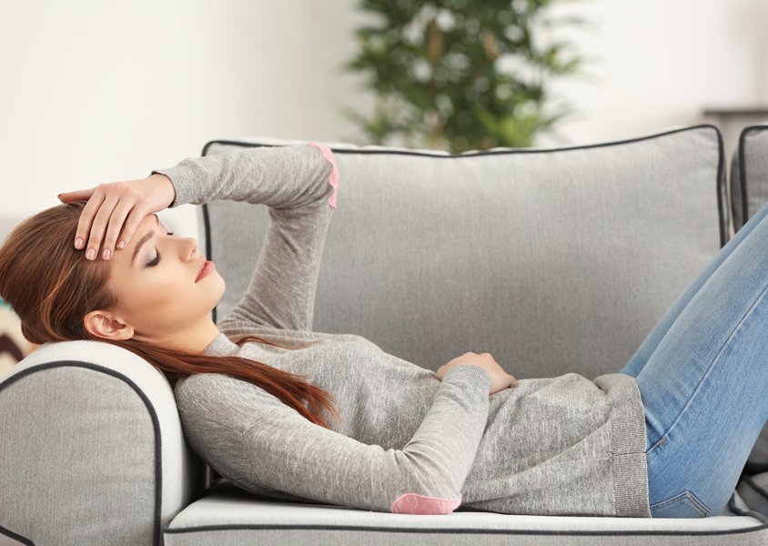 Woman laying on couch holding her forehead