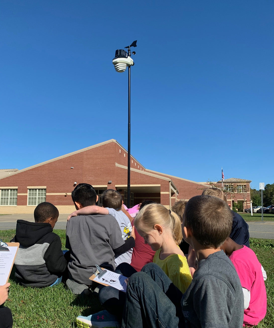 Elementary class filling out worksheets in front of AcuRite Atlas Weather Station