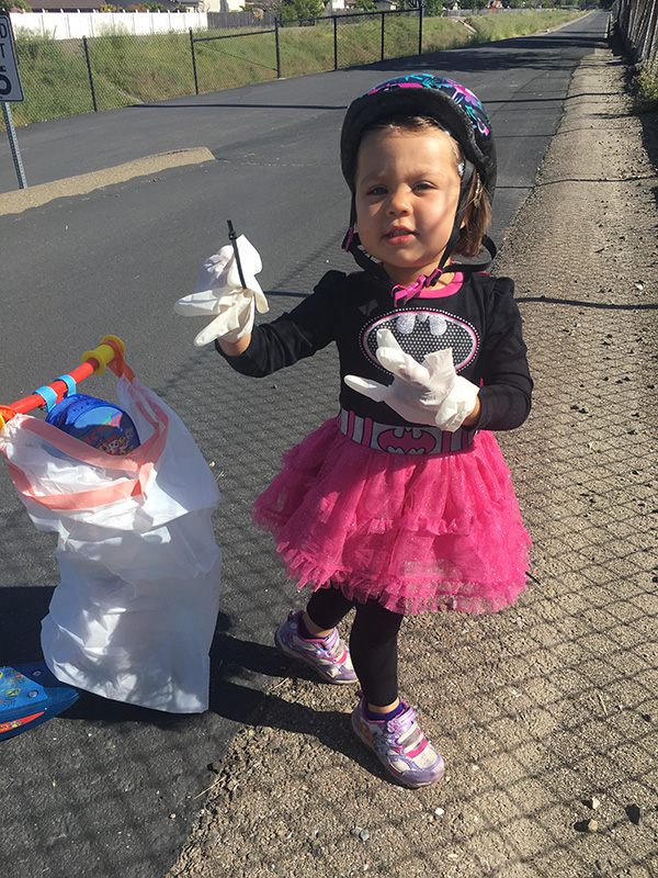 Child with protective gloves picking up trash