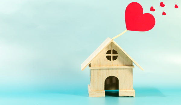 Wooden toy-size home against a blue background with red hears at the top left side of the image