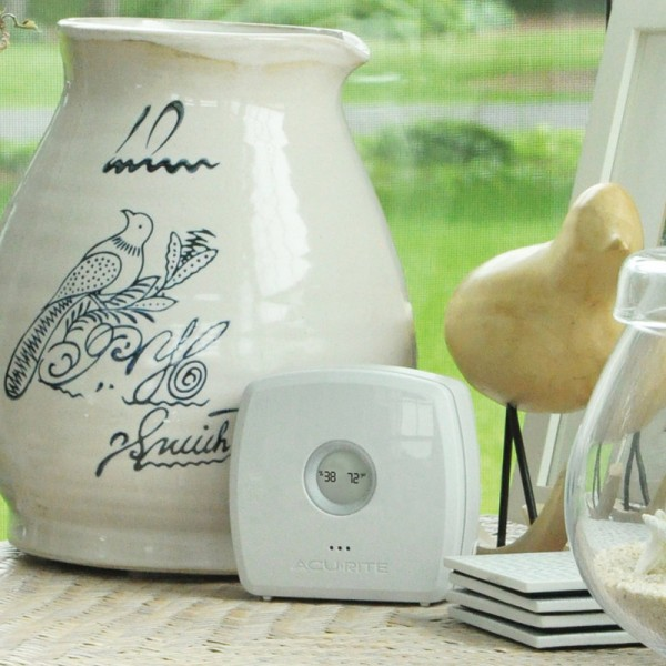 AcuRite Room Monitor on a table with pottery and home decorations