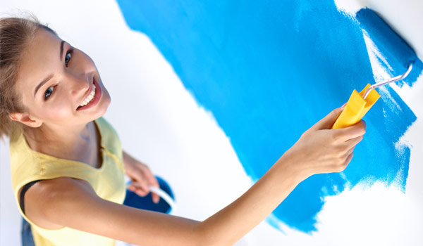 Woman smiling and painting a wall with blue paint using a paint roller