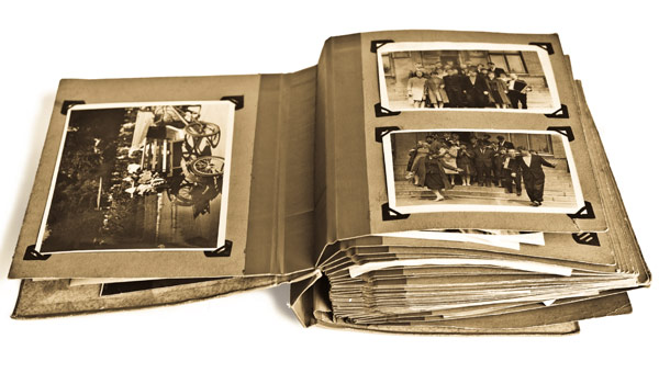 Old sepia tone photo album open to pages showing three photos