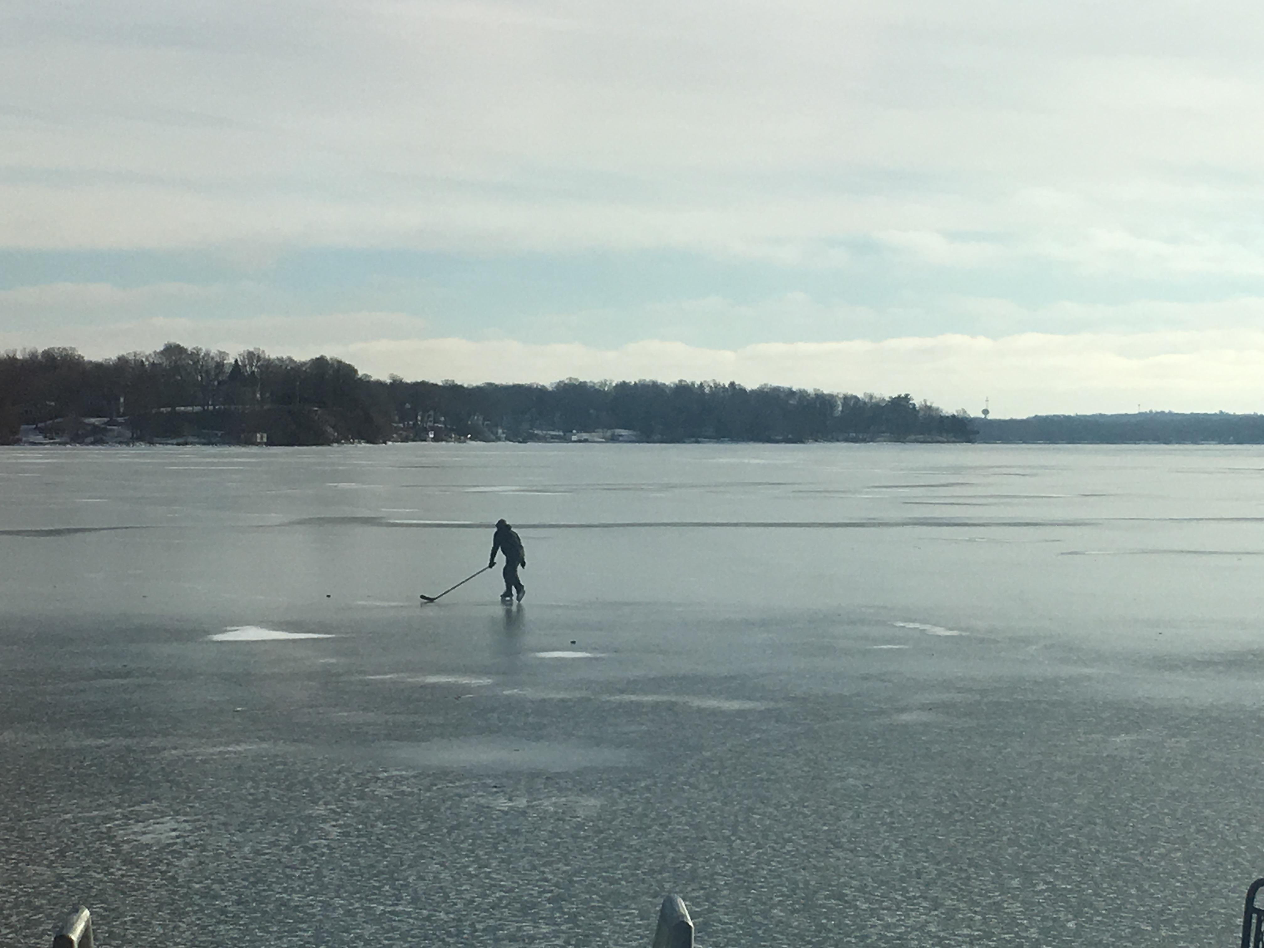 Single hockey player on a frozen lake
