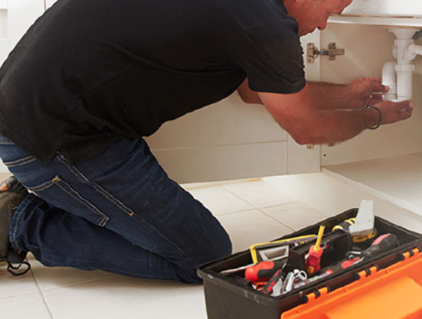 Man working on the pipes under a sink with a toolbox in the foreground