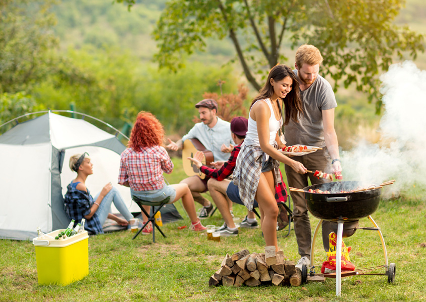 Group of people camping and grilling outdoors