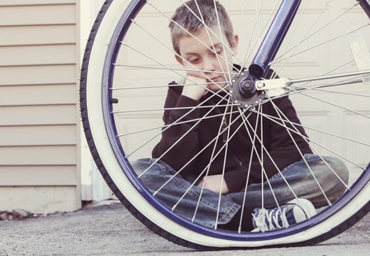 Child looking at flat tire of bicycle