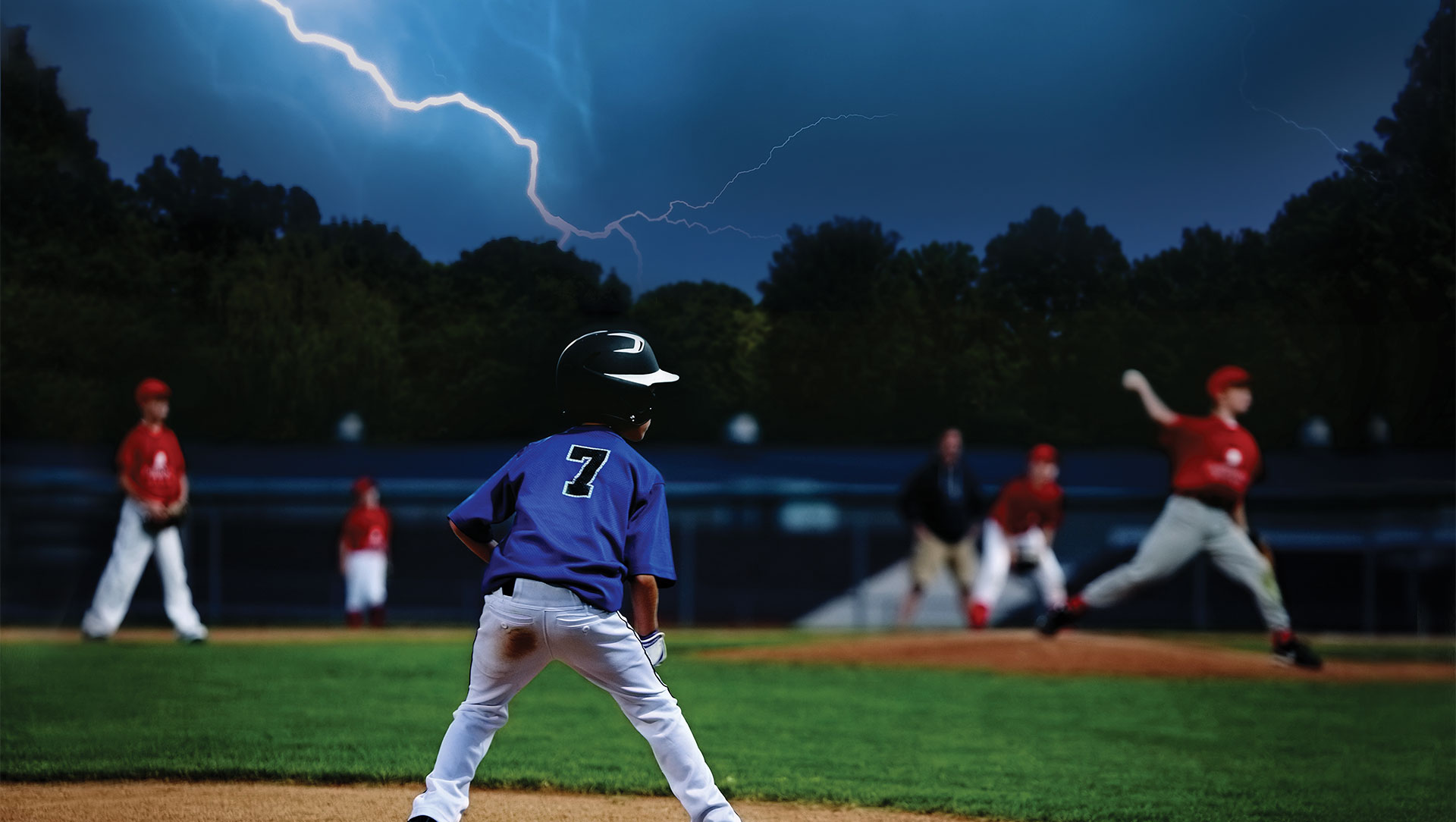 Children's baseball game with lightning in the sky
