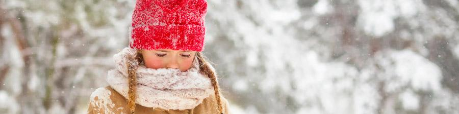 Child outside in winter clothes, including a red winter hat and scarf